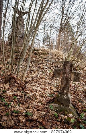 Old tombstone cross of the First World War overgrown with moss and old leaves in the autumn forest stock photo