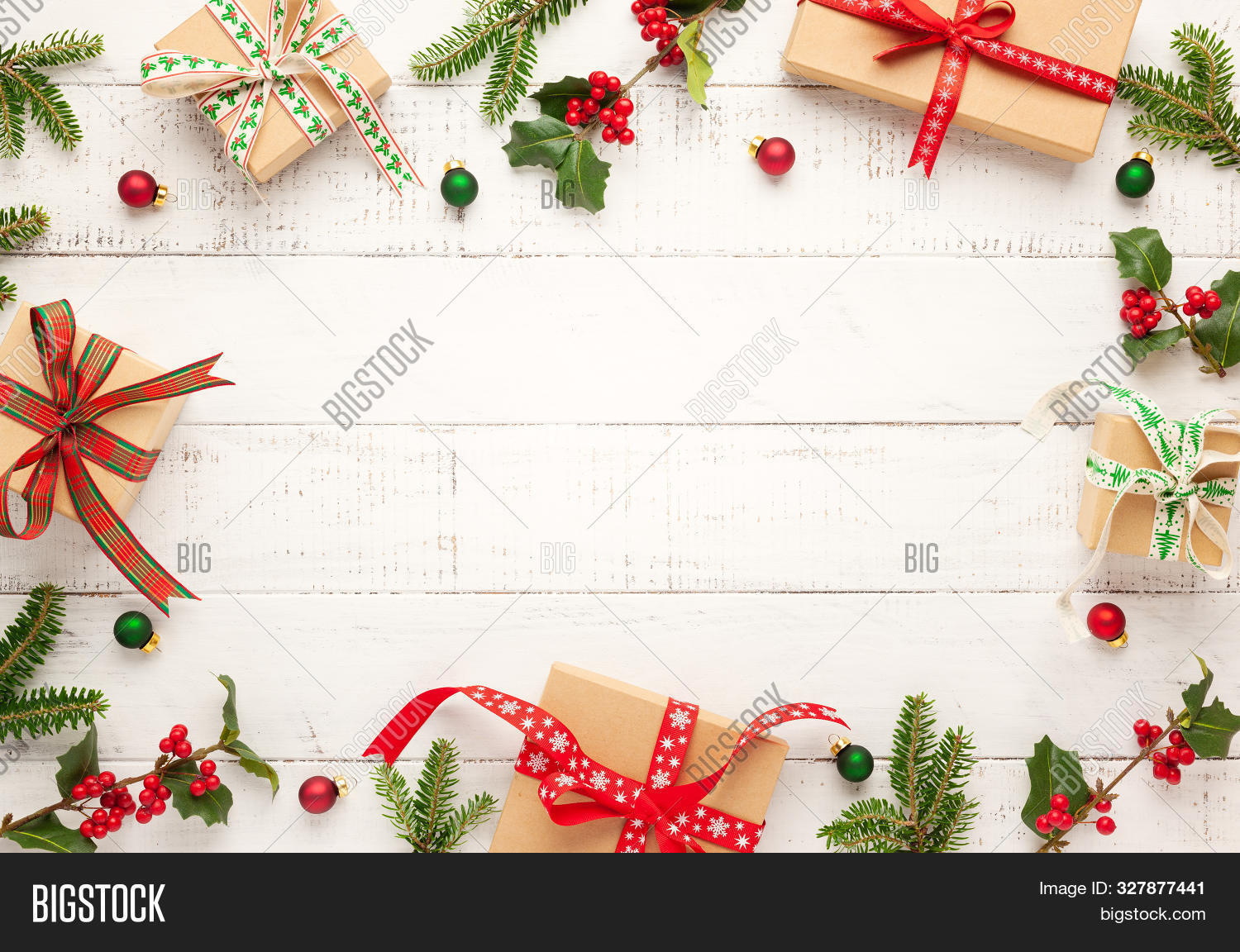 Christmas background with gift boxes, Christmas decorations and branches of holly and fir on white wooden background. Winter festive concept. Flat lay, copy space.
