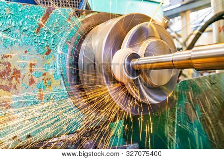 Grinding metal, abrasive wheel at high speeds removes part of the metal on the machined surface of a round part. stock photo
