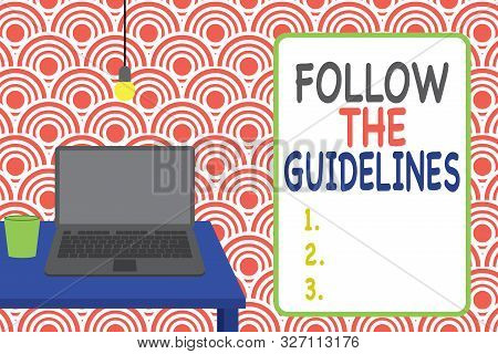 Conceptual hand writing showing Follow The Guidelines. Business photo showcasing Manual of Style Follow a Specified Rule Accordingly Front view laptop lying on wooden desktop light bulb glass. stock photo
