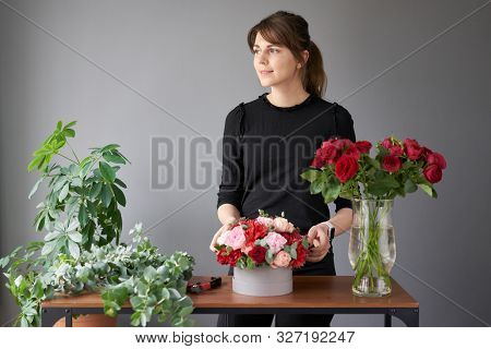 Florist woman creates flower arrangement in a round box. Beautiful bouquet of mixed flowers. Floral shop concept . Handsome fresh bunch. Flowers delivery stock photo
