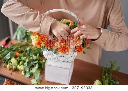 Florist woman creates flower arrangement in a wicker basket. Beautiful bouquet of mixed flowers. Floral shop concept . Handsome fresh bouquet. Flowers delivery stock photo