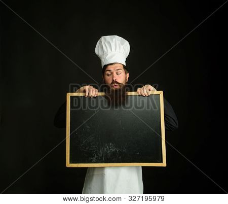 Advertising chef menu. Bearded chef holds blackboard. Restaurant chef show empty chalkboard. Blank chalkboard with copy space for text. Male chef, cook or baker with blank board. Business lunch menu stock photo