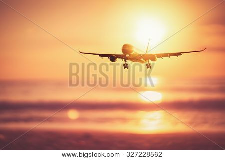 Airplane flying over tropical beach with smooth wave and sunset sky abstract background. Copy space of business summer vacation and travel adventure concept. Vintage tone filter effect color style. stock photo
