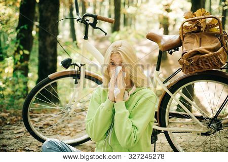 Young blonde in a green sweater sitting on the ground in the park blowing her nose on bicycle background. Seasonal allergy. Woman handkerchief sneezing because of allergy. Blonde allergic reaction relax forest. Girl bicycle in nature. Woman bicycle autumn stock photo