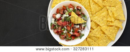 Pico de Gallo with gluten free tortilla chips on a black surface, top view. Flat lay, overhead, from above. Copy space. stock photo
