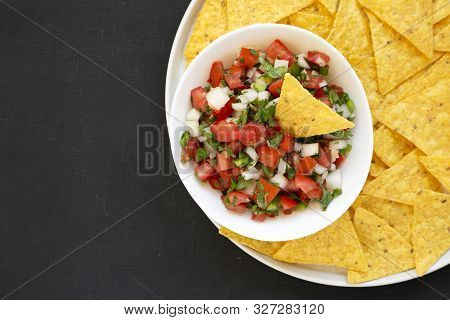 Pico de Gallo with gluten free tortilla chips on a black background, top view. Flat lay, overhead, from above. Copy space. stock photo