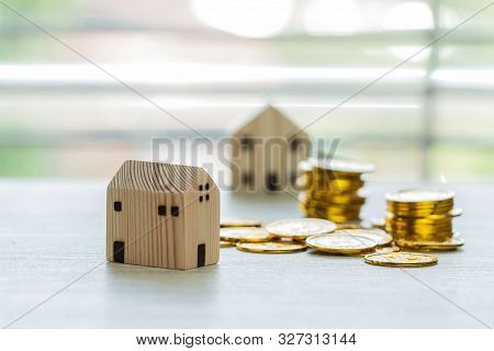 Finance business real estate investment concept, House model with stack money coins. miniature wooden home show for selling. Ideas for offers of mortgage investment, building to buy new residential stock photo