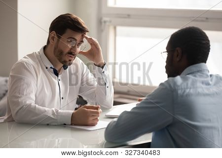 Confused young hr manager listening to african american job applicant. stock photo