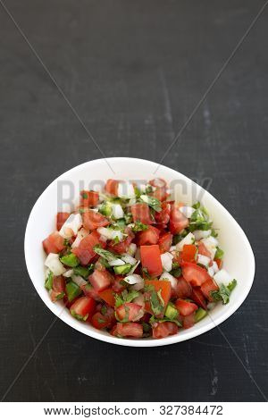Pico de Gallo in a white bowl on a black background, low angle view. Copy space. stock photo