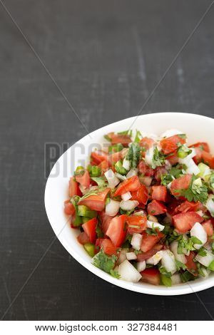 Pico de Gallo in a white bowl on a black surface, low angle view. Space for text. stock photo