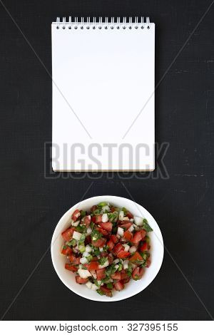 Pico de Gallo in a white bowl, blank notebook on a dark background, top view. Overhead, from above, flat lay. Space for text. stock photo