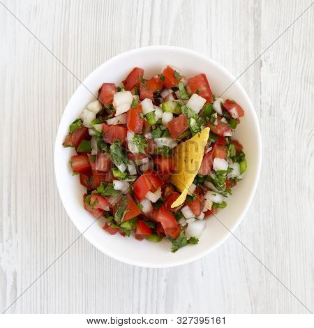 Pico de Gallo in a white bowl on a white wooden table, top view. Overhead, from above, flat lay. Close-up. stock photo