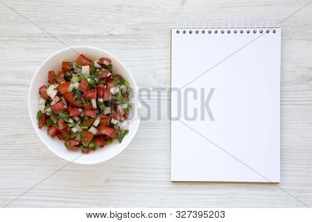 Pico de Gallo in a white bowl, blank notepad on a white wooden surface, top view. Overhead, from above, flat lay. Copy space. stock photo