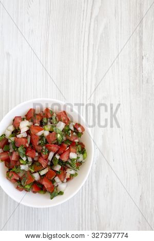Pico de Gallo in a white bowl on a white wooden background, top view. Overhead, from above, flat lay. Copy space. stock photo
