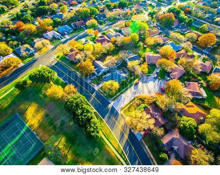 Golden hour sun rays sunrise suburbia houses and homes aerial drone view above suburb new development in Austin Texas USA stock photo