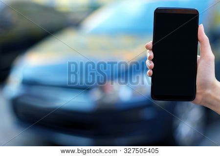 Closeup female hand is holding  smartphone with blank screen display. Black car automobile on street parking on blurred background. Online application, software for using by drivers concept. stock photo