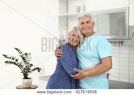 Portrait of affectionate senior couple in kitchen. Space for text stock photo