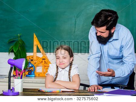 Strict pedagogue. Doing hometask paperwork. Tired kid unmotivated study learn. Private lesson. Homeschooling with father. Pedagogue skills. School teacher and schoolgirl. Man bearded pedagogue stock photo