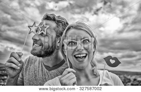 Feeling playful. Couple in love enjoy party time on cloudy sky. Sexy woman and sexi man wear fake glasses accessories. Funny couple in party photobooth props. Photo booth party celebration stock photo