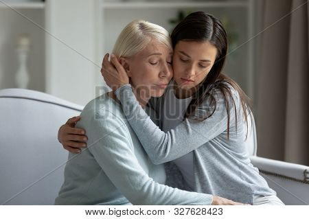 Millennial upset lady calming soothing depressed middle aged mother. stock photo