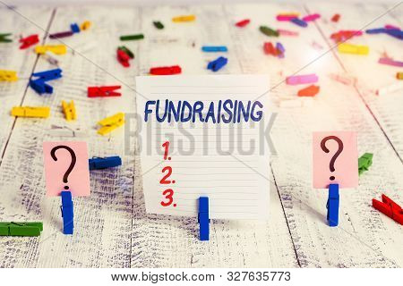 Text sign showing Fundraising. Conceptual photo act of collecting or producing money for a particular purpose Scribbled and crumbling sheet with paper clips placed on the wooden table. stock photo