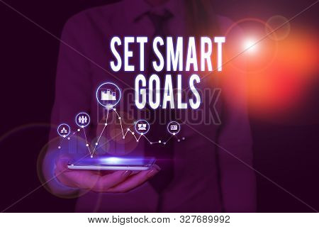Text sign showing Set Smart Goals. Conceptual photo giving criteria to guide in the setting of objectives Woman wear formal work suit presenting presentation using smart device. stock photo