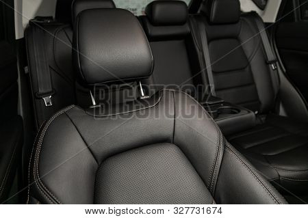 Close-up rear seat made of black leather with a head restraint, in the background passenger seats with seat belts. Luxury car interior stock photo