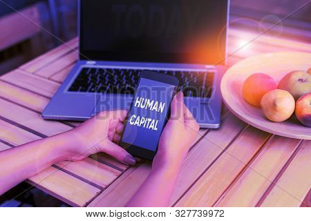 Conceptual hand writing showing Huanalysis Capital. Business photo showcasing Intangible Collective Resources Competence Capital Education woman with laptop smartphone and office supplies technology. stock photo
