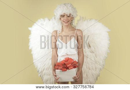Girl with angel wings and a white dress. Cupid woman. Angel woman with feather white wings and gift. Beautiful woman posing with angel wings stock photo