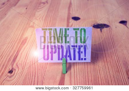 Writing note showing Time To Update. Business photo showcasing act updating something someone or updated version program Wooden floor background green clothespin groove slot office. stock photo