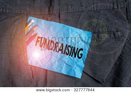 Text sign showing Fundraising. Conceptual photo act of collecting or producing money for a particular purpose Writing equipment and blue note paper inside pocket of man work trousers. stock photo