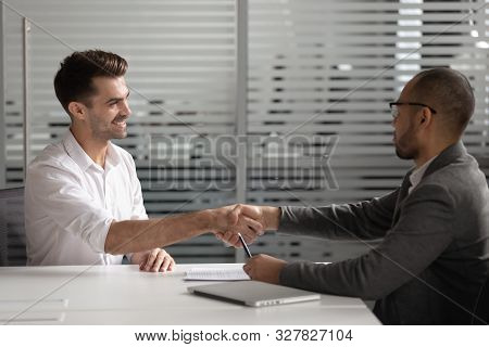 African American recruiter shaking hand of Caucasian candidate at interview stock photo