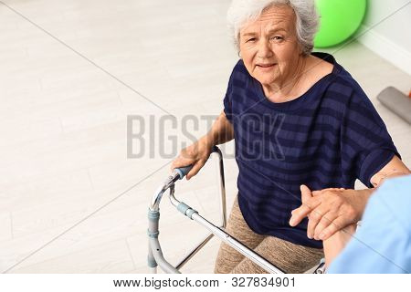 Caretaker helping elderly woman with walking frame indoors stock photo