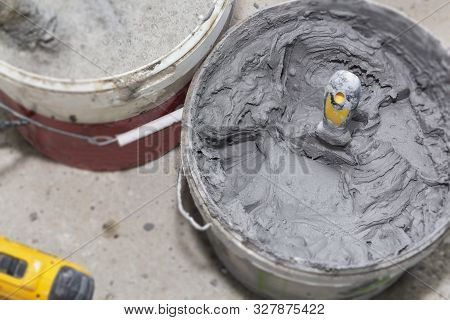 Decorative cement plaster and a trowel in a construction bucket ready for plastering stock photo
