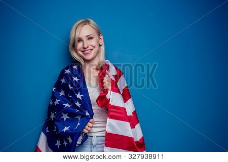 blonde woman in jeans holding American flag with paper crown and torch Statue of liberty on a blue background in the studio .4th july independence day celebration concept stock photo
