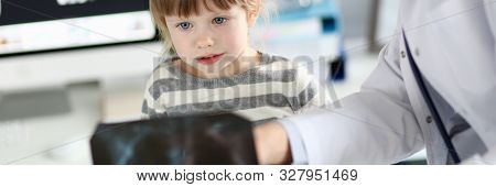Portrait of concentrated child looking at radiogram shot of lungs. Professional doctor showing black fluorography to interested girl kid. Clinic checkup and healthcare concept stock photo