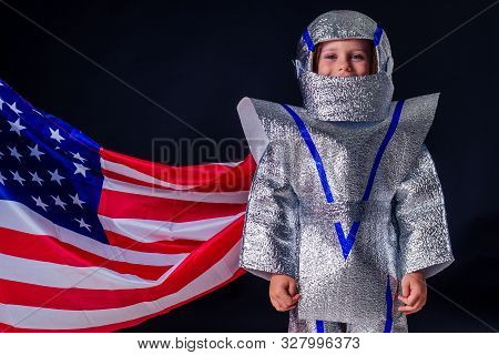 adorable female child in costume helmet playing bright foil silver cosmonaut in uniform with american flag black background in the studio.patriotism July 20, 1969 landing on the moon concept space day stock photo