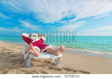 sunbathing Santa Claus relaxing in bedstone on tropical sandy beach - Christmas concept stock photo