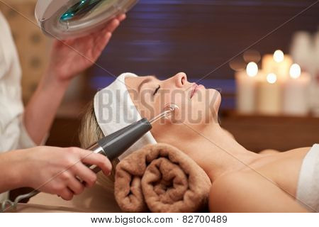 people, beauty, spa, cosmetology and technology concept - close up of beautiful young woman lying wi