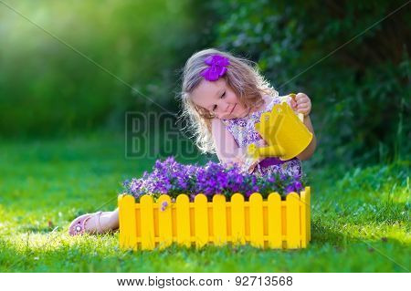 Little Girl Working In The Garden Watering Flowers