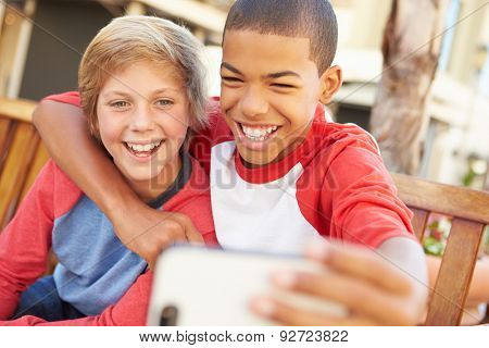 Two Boys Sitting On Bench In Mall Taking Selfie stock photo