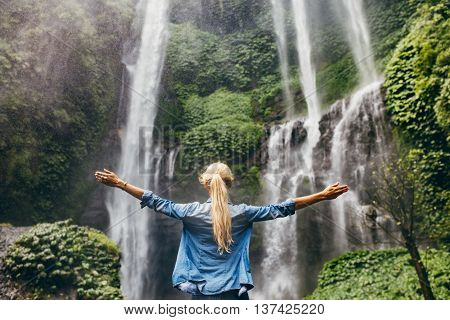 Woman Standing By Waterfall With Her Hands Raised