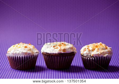 three chocolate velvet cupcakes with vanilla icecream topping isolated on purple background stock photo