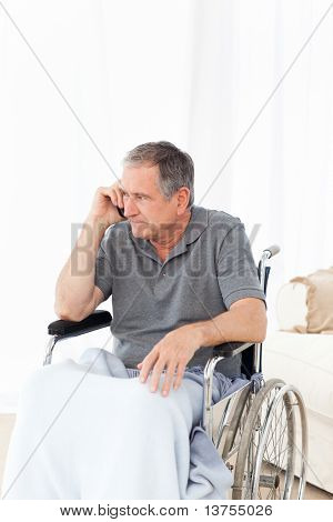 Senior in his wheelchair phoning at home stock photo