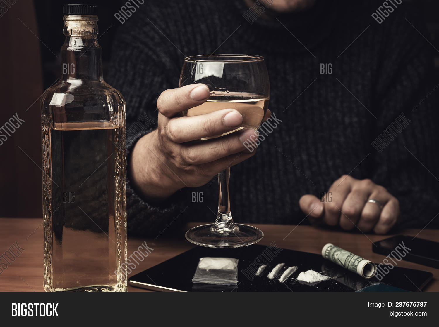 Man holds glass of whiskey and uses cocaine drugs. Drug abuse and alcoholism concept, toned