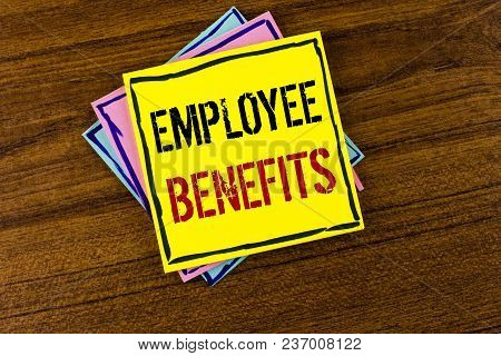 Writing note showing  Employee Benefits. Business photo showcasing list of advantage recruiter get at work Insurance written Yellow Sticky Note Paper the Wooden background. stock photo