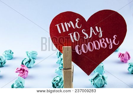 Handwriting text Time To Say Goodbye. Concept meaning Separation Moment Leaving Breakup Farewell Wishes Ending written Red Paper Heart holding by Clip plain background Paper Balls next to it. stock photo