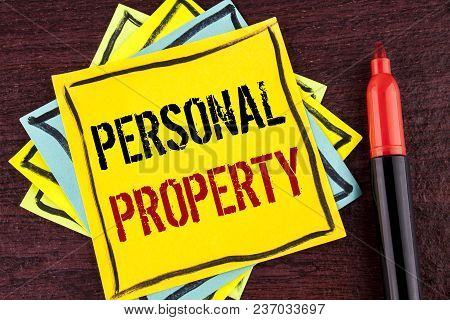 Handwriting text Personal Property. Concept meaning Belongings possessions assets private individual owner written Yellow Sticky note paper wooden background Marker next to it. stock photo