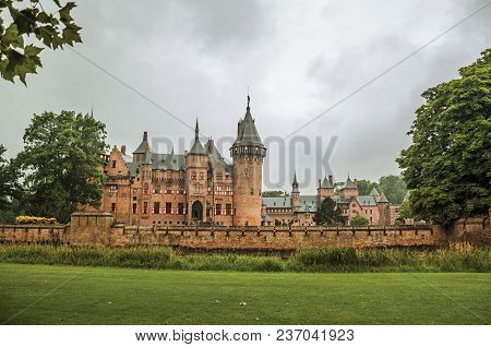 De Haar Castle with ornate brick towers, lawn wooded gardens and rainy day, near Utrecht. Of medieval origin, it underwent reforms until assuming a richly decorated Gothic style. Northern Netherlands. stock photo